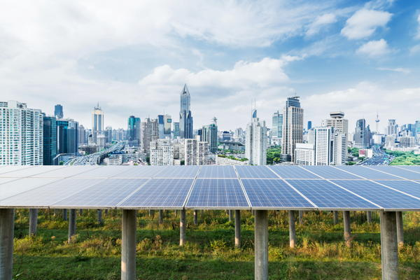 Solar panels with a modern city in the background
